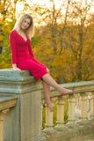 Piękna kobieta w czerwieni smokingowym i starym arhitecture na spadek natury tle Obrazy Stock