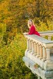 Piękna kobieta w czerwieni smokingowym i starym arhitecture na spadek natury tle Fotografia Stock