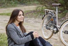Piękna kobieta z rowerowym obsiadaniem w parku Zdjęcia Stock