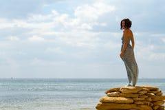 Piękna kobiety pozycja na kamieniach z morza i nieba backgro Zdjęcia Royalty Free