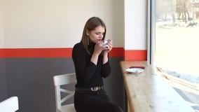 Pi?kna ?liczna dziewczyna w kawiarni blisko okno, pije kaw? i ono u?miecha si? zbiory