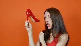 Pi?kna m?oda br?zowow?osa dziewczyna egzamininuje par? czerwoni buty emocje Sztuka portret w studiu na pomara?cze zbiory wideo