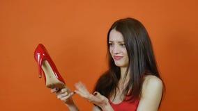 Pi?kna m?oda br?zowow?osa dziewczyna egzamininuje par? czerwoni buty emocje Sztuka portret w studiu na pomara?cze zdjęcie wideo
