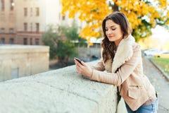 Pi?kna m?oda brunetki dziewczyna chodzi przez jesieni miasta w promieniach ciep?y ?wiat?o s?oneczne zdjęcie stock