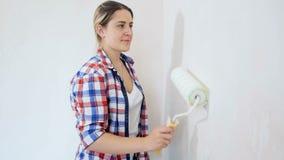 Pi?kna m?oda kobieta renovaating jej nowego mieszkanie M?oda dziewczyna obrazu ?ciany przy jej pokojem zbiory wideo