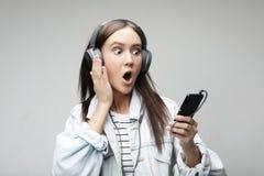 Pi?kna m?oda kobieta s?ucha muzyka w he?mofonach z smartphone obrazy stock