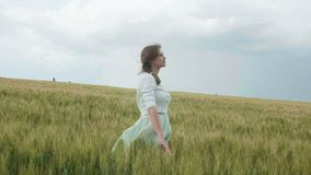 Pi?kna m?oda rosyjska dziewczyna w?r?d wysokich zielonych spikelets banatka w polu Zbiera spikelets w plikach Dziewczyny enj zbiory wideo
