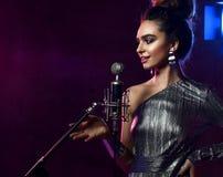 Pi?kna ?piewacka dziewczyna k?dzierzawy afro w?osiany piosenkarz ?piewa z mikrofonu karaoke piosenk? na scenie na ciemnym neonowy obraz stock