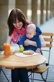 Piękna potomstwo matka z jej dzieckiem w kawiarni Fotografia Stock