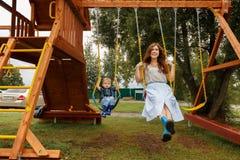 Pi?kna rodzina ma zabaw? outside Rodzice z dziećmi jedzie na huśtawce Mama bawić się z jej małym synem na tarasie obraz stock