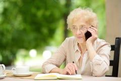 Pi?kna starsza dama z k?dzierzawym bia?ym w?osy pracuje w outdoors restauraci lub kawiarni Starsi dama style ?ycia zdjęcie stock