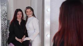 Pi?kna studio Beautician ocenia pacjenta, spojrzenia przy twarzą, wtedy obraca w lustrze wpólnie one 4K zwalniaj? zbiory