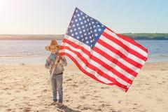 Pi?kna szcz??liwa dziewczyna z zielonymi oczami z flag? ameryka?sk? na jaskrawym s?onecznym dniu Dziewczyna w kowbojskiego kapelu zdjęcie stock