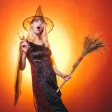 Pi?kna zdziwiona kobieta w czarownicach kapelusz i kostiumu - pokazywa? produkty Halloweenowa kobieta W górę portreta wspaniały obrazy stock