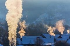 Piękna zimy sceneria z dymnym przybyciem od domowych kominów na jaskrawym, zimnych, ranek, w dalekiej wsi w Europa Obrazy Stock