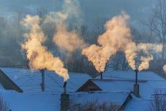 Piękna zimy sceneria z dymnym przybyciem od domowych kominów na jaskrawym, zimnych, ranek, w dalekiej wsi w Europa Obraz Stock