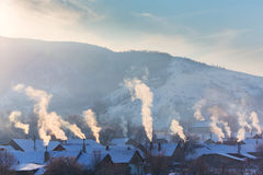 Piękna zimy sceneria z dymnym przybyciem od domowych kominów na jaskrawym, zimnych, ranek, w dalekiej wsi w Europa Zdjęcia Royalty Free
