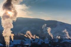 Piękna zimy sceneria z dymnym przybyciem od domowych kominów na jaskrawym, zimnych, ranek, w dalekiej wsi w Europa Fotografia Stock
