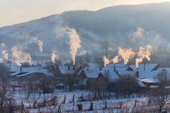 Piękna zimy sceneria z dymnym przybyciem od domowych kominów na jaskrawym, zimnych, ranek, w dalekiej wsi w Europa Zdjęcie Stock