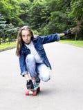 Pięknej blondynki nastoletnia dziewczyna w cajg koszula na deskorolka w parku, Zdjęcie Royalty Free