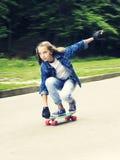 Pięknej blondynki nastoletnia dziewczyna w cajg koszula na deskorolka w parku, Zdjęcie Stock