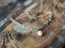 Pięknej perełkowej kolii kierowy kształt na eleganckim drewnianym tle odizolowywający nad biel pojęcie prezent obraz stock