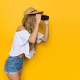 Piękni kobiet spojrzenia Przez lornetek Obraz Stock
