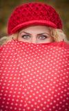 Piękni niebieskie oczy nad kolorowym parasolem. Atrakcyjna blondynki dziewczyna patrzeje nad czerwony parasolowy plenerowym z czer Obrazy Stock