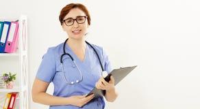 Pi?kni u?miechni?ci kobiety lekarki stojaki w medycznym biurze i przedstawienia lubi? Opieki zdrowotnej poj?cie, ubezpieczenie me fotografia stock