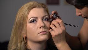 Pi?kno bar M?ody pi?kny dziewczyna model siedzi w krze?le Makeup artysta robi dziewczyny makeup Blondynka w pi?knie zbiory wideo