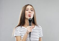 Pi?kno dziewczyny wzorcowy piosenkarz z mikrofonem nad jasnopopielatym t?em zdjęcie stock