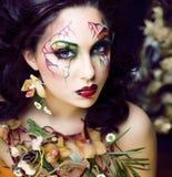 Pi?kno kobieta z twarzy sztuk? i bi?uteria od kwiat orchidei up, kreatywnie deseniowego makeup kwiecistego deseniowego t?a zamkni zdjęcia stock