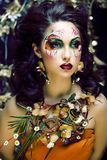 Pi?kno kobieta z twarzy sztuk? i bi?uteria od kwiat orchidei up, kreatywnie makeup kwiecistego deseniowego t?a zamkni?tego, obraz stock