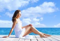 Piękny, atrakcyjny model pozuje w biel sukni na drewnianym pi, Obrazy Royalty Free