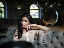 Pi?kny brunetka model siedzi przy sto?em w restauracji i trzyma r?k? stawia? czo?o Wzorcowa fotografia zdjęcia royalty free