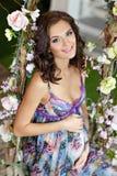 Piękny brunetki dziewczyny czekanie dla dziecka w purpury sukni siedzi Obrazy Royalty Free