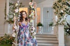 Piękny brunetki dziewczyny czekanie dla dziecka w purpury sukni siedzi Zdjęcia Royalty Free