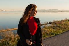 Pi?kny brunetki kobiety portreta sta? outside w s?onecznym dniu z jeziorem w tle, zdjęcie royalty free