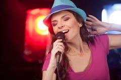 Piękny dziewczyny mienia mikrofon i pozycja w barze Fotografia Stock