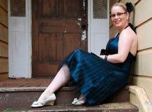 Piękny dziewczyny obsiadanie na krokach w koktajl sukni Zdjęcie Royalty Free