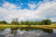 Pi?kny jezioro z drzewami na bia?ych bufiastych chmurach w niebie i horyzoncie wci?? Pokojowy letni dzie? przy cha?up? Ampu?y zie zdjęcie stock
