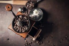 Piękny kawowy ostrzarz i kawowa fasola na starym kuchennym stole Fotografia Stock