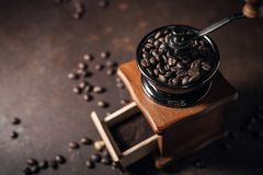 Piękny kawowy ostrzarz i kawowa fasola na starym kuchennym stole Zdjęcie Royalty Free