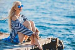 Piękny kobiety obsiadanie blisko morza Zdjęcie Royalty Free
