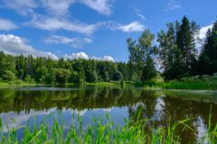 Piękny lato krajobraz z widokiem na jeziorze z odbicie bielem i niebieskim niebem chmurnieje zdjęcie stock
