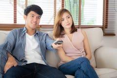 Pi?kny m?ody azjatykci pary mienia pilot, dopatrywanie tv i wideo leje si? na kanapie z relaksujemy i szcz??liwy zdjęcia royalty free