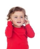 Piękny małego dziecka dwa lat dotyka jego ucho zdjęcie royalty free