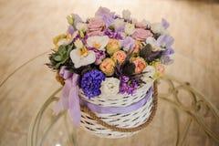 Piękny purpurowy bukiet mieszani kwiaty w koszu na stole Fotografia Stock