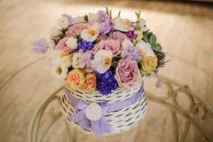 Piękny purpurowy bukiet mieszani kwiaty w koszu na stole Zdjęcie Stock