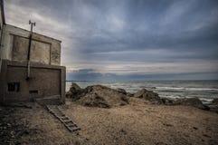 Piękny surrealistyczny krajobraz zaniechany dom i drabina na skalistym seashore przy zmierzchu czasem Chmurna pogoda Morze Kaspij Zdjęcie Royalty Free